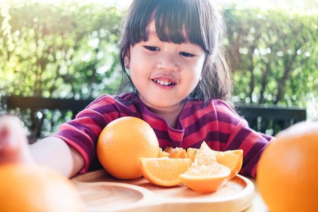 Kleine nette 3-4 jahre alte mädchen mit geschnittener orange auf hölzerner platte