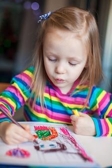 Kleine nette mädchenmalerei mit bleistiften beim sitzen an ihrem tisch