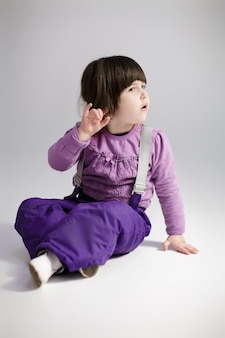 Kleine niedliche mädchenbrünette in einem lavendelpullover und in der hose, die versuchen, auf grauem hintergrund zu hören