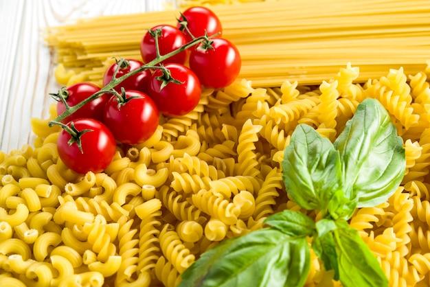 Kleine nudeln für suppen, lockige nudeln und basilikumblatt mit tomaten auf dem tisch