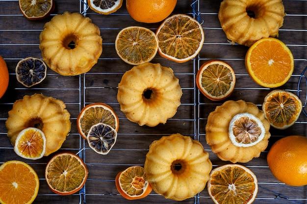 Kleine orange bundt-kuchen mit den frischen und trockenen orangen auf abkühlendem rücken, draufsicht, flache lage
