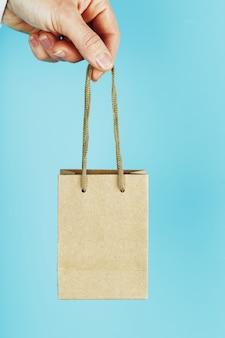 Kleine papiertüte auf armeslänge, braune basteltasche zum mitnehmen lokalisiert auf blauem hintergrund. layout der verpackungsvorlage mit platz zum kopieren, für werbung.