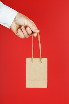 Kleine papiertüte auf armeslänge, braune basteltasche zum mitnehmen lokalisiert auf rotem hintergrund. layout der verpackungsvorlage mit platz zum kopieren, für werbung.