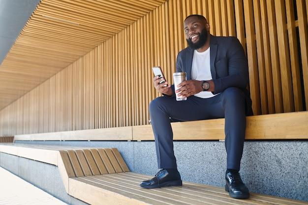 Kleine pause. bild von einem mann mit einem telefon und einer flasche wasser in der hand