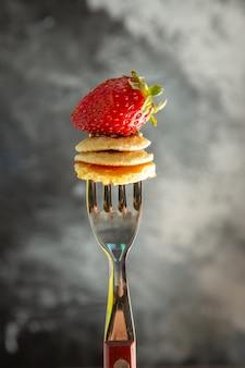 Kleine pfannkuchen der vorderansicht mit erdbeere auf gabel und grauem schreibtischkuchenfruchtfutter