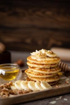 Kleine pfannkuchen mit banane, walnüssen und honig auf einem holztablett