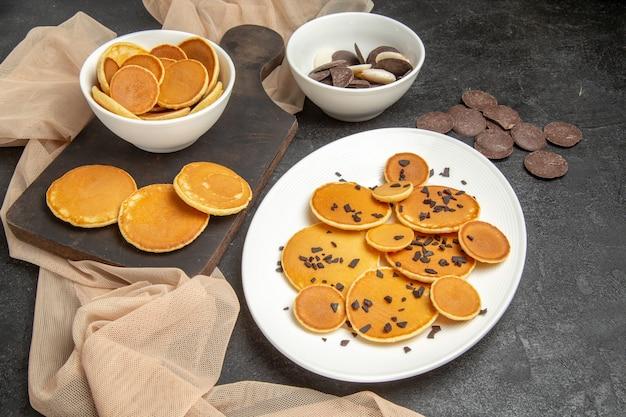 Kleine pfannkuchen mit keksen auf dunkelgrau