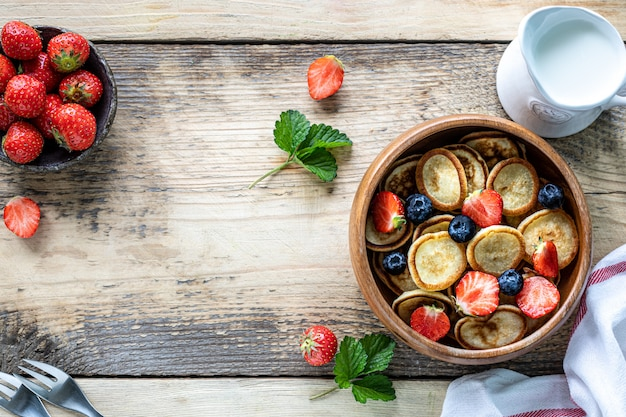 Kleine pfannkuchen müsli und schokolade mini pfannkuchen in einer holzschale mit honig und erdbeeren