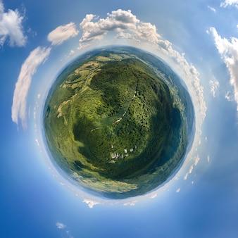 Kleine planetenkugel mit dunklen berghügeln, bedeckt mit grüner mischkiefer und üppigen wäldern, umgeben von klarem blauem himmel mit weißen wolken.