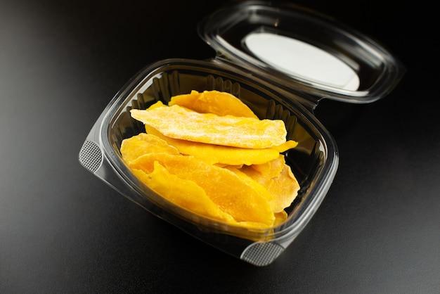 Kleine plastikbox oder auflauf mit scheiben getrockneter mango auf schwarzem hintergrund