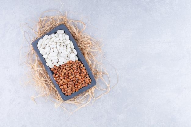 Kleine platte auf einem strohhaufen, gefüllt mit roten bohnen und dunkelblauen bohnen auf marmoroberfläche