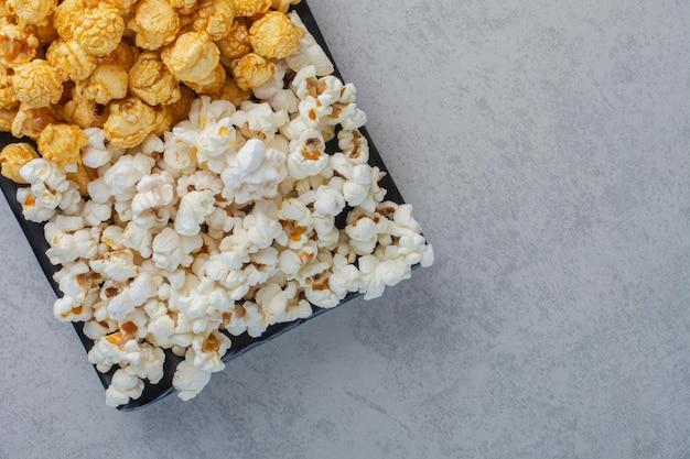 Kleine platte mit popcornbonbons und salzigem popcorn auf marmoroberfläche
