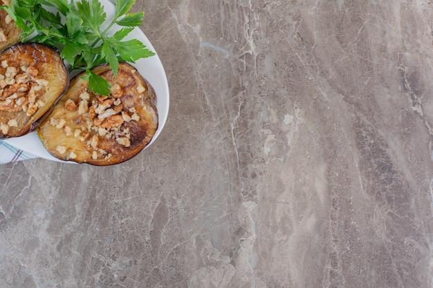 Kleine portion gebratener indischer auberginenscheiben, garniert mit gehacktem knoblauch und petersilie, auf marmor.