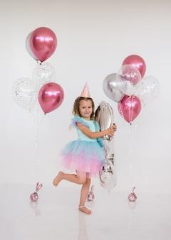 Kleine prinzessin mädchen steht mit luftballons auf weißem hintergrund mit platz für text. geburtstagsfeier