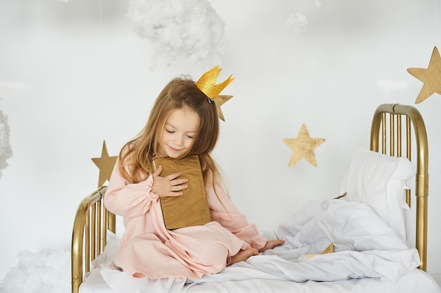 Kleine prinzessin mit einem magischen stab auf einem bett in einer wolke auf einem weißen hintergrund