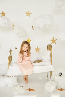 Kleine prinzessin mit einem zauberstab auf einem bett in einer wolke auf einem weißen hintergrund
