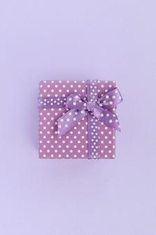 Kleine purpurrote geschenkbox mit band liegt auf einem violetten hintergrund.