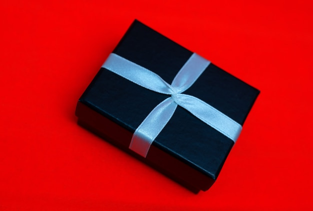Kleine rechteckige schwarze geschenkbox auf rotem grund