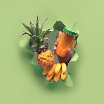 Kleine reife orange ananas in der menschlichen hand, die andere hand zeigt ok-zeichen. hände mit den früchten zeigen sich aus zerrissenem papierloch.