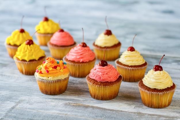 Kleine reihen cupcakes desserts mit buntem zuckerguss kleine wunder des kochgeschmacks, die sie mögen