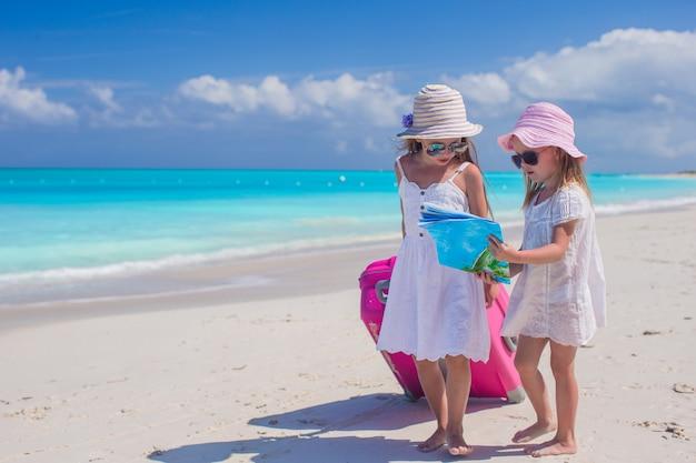 Kleine reizende mädchen mit großem koffer und einer karte auf tropischem strand