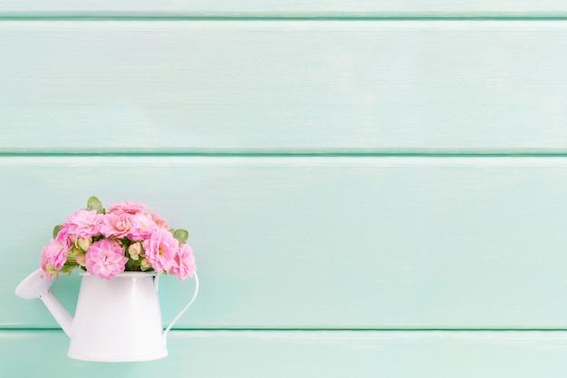 Kleine rosa blüten in dekorativer vase.