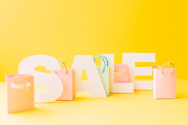 Kleine rosa einkaufstasche mit verkaufswort auf gelbem hintergrund