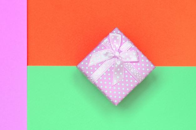 Kleine rosa geschenkboxlüge auf buntem papier
