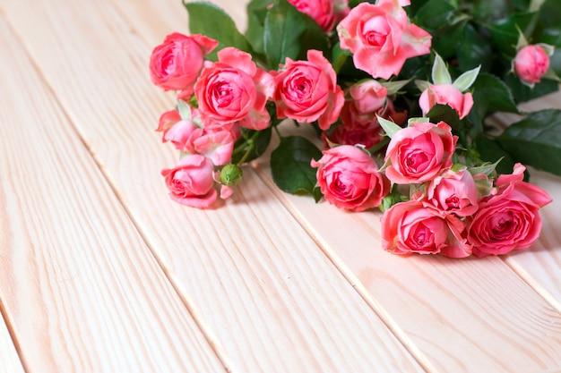 Kleine rosa rosen auf einem hölzernen hintergrund