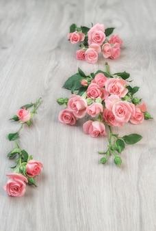 Kleine rosa rosen auf holztisch,