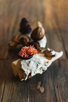 Kleine rote blumen in der schwarzen schale auf hölzernem klotz der natürlichen form über holztisch. restaurant tisch objekt dekoration.