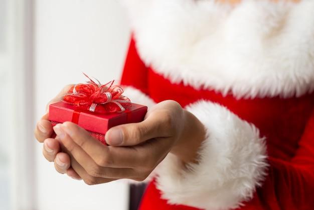 Kleine rote geschenkbox mit spitzen- bogen in weiblichen händen