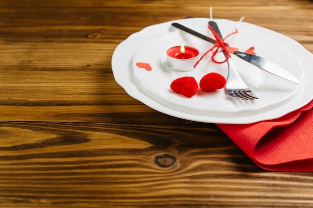 Kleine rote herzen mit tischbesteck auf platte