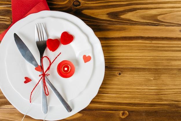 Kleine rote herzen mit tischbesteck auf weißer platte