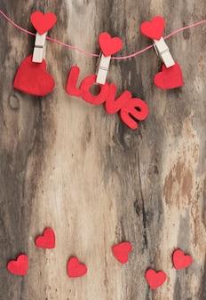Kleine rote herzen und rote wortliebe hängen an hölzernen wäscheklammern auf hölzernem hintergrund. karte mit kopierplatz. vertikale ausrichtung. hohe auflösung
