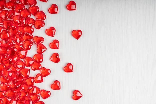 Kleine rote herzformbonbons, die auf weißem holz liegen, legen in einem bündel auf der linken seite