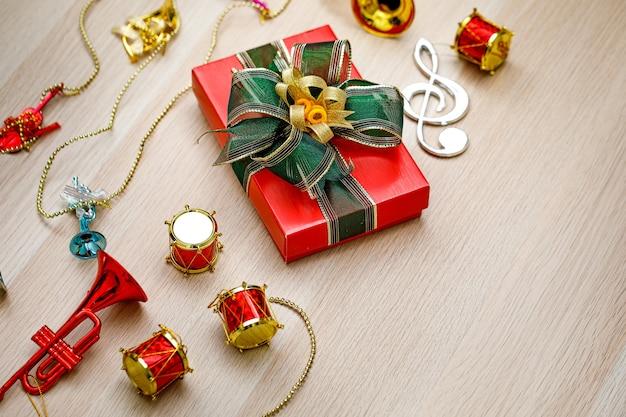 Kleine rote papierverpackte geschenkbox mit grün-goldener glänzender bandfliege auf holztisch mit kleinen dekorativen musikinstrumenten an heiligabend-geburtstagsnacht oder neujahrsfest.