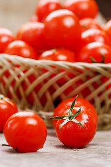Kleine rote tomaten in einem weidenkorb auf einem alten holztisch. reife und saftige kirsche