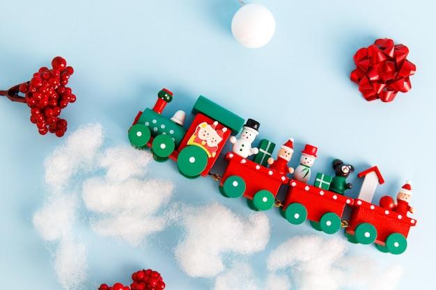 Kleine rote weihnachtsspielzeugbahn auf blauem hintergrund