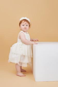 Kleine rothaarige babyfrau spielt auf einem beigen raum