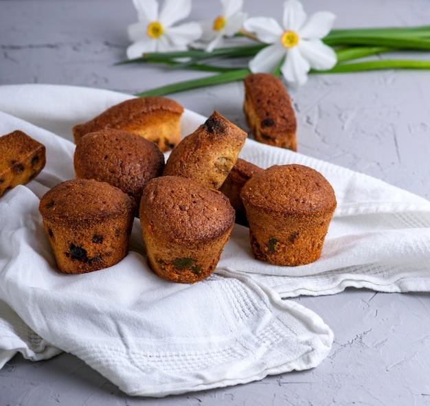 Kleine runde gebackene muffins mit trockenen früchten und rosinen auf einer weißen textilserviette