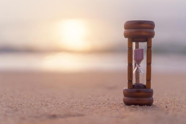 Kleine sanduhr-showzeit fließt auf sandstrandhintergrund.