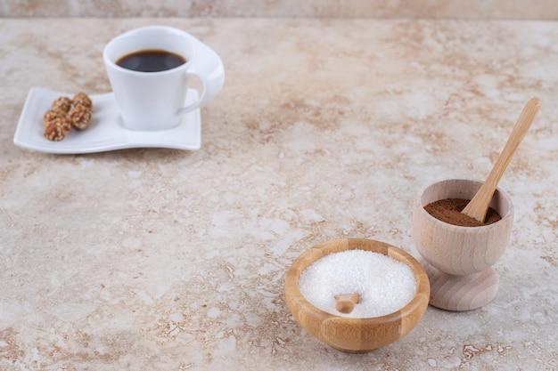 Kleine schalen mit gemahlenem kaffeepulver und zucker neben einer tasse kaffee und glasierten erdnüssen