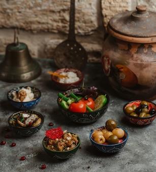 Kleine schalen mit turshu, gemüse und snacks.