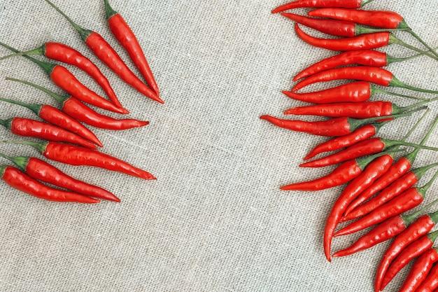 Kleine scharfe chilischoten auf sackleinen. draufsicht, flach zu legen. essen mit roter paprika und freiem platz in der mitte des rahmens