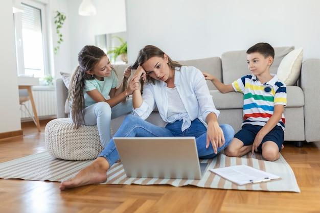 Kleine schelmische kinder, die lärmende und ablenkende mutter-freiberuflerin versuchen, sich auf den laptop zu konzentrieren und den kopf zu drücken, der im hellen wohnzimmer am tisch arbeitet