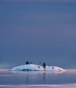 Kleine schneebedeckte insel im wintersee ladoga in karelien