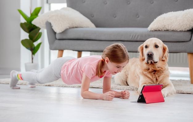 Kleine schöne frau, die in plankenposition während des online-yoga auf tablette mit goldenem retriever bleibt