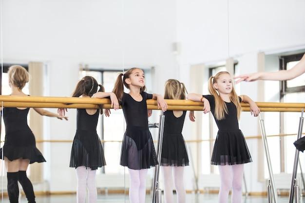 Kleine schöne süße mädchen kinder im studio trainieren mit einem trainer bei einer tanzstunde.
