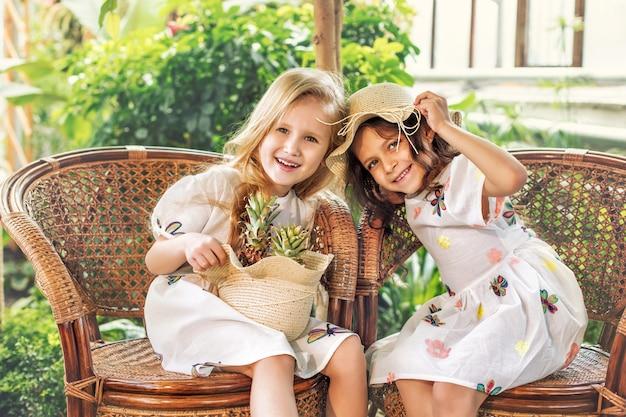 Kleine schöne süße mädchen kinder in weißen kleidern mit ananas in den händen auf tropischen pflanzen
